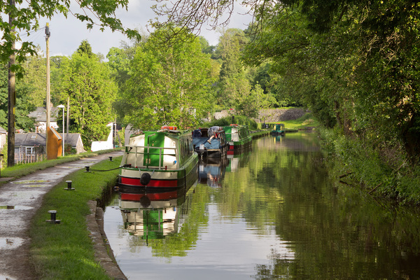 Canal with boats: Barges and narrowboats on a canal in eastern Wales.