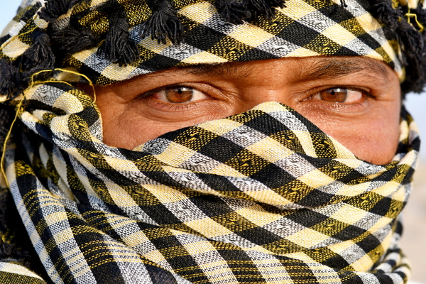 Head scarf on Indian man: Arabic Indian man in desert with head scarf a traditional culture that is going on for hundreds and hundreds of years in the Arabic countries and in Saudi Arabia . Photos in desert on the desert hill with sand only in the area and everywhere in the backgr
