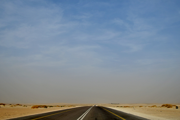 Driving on a desert road: Driving on a desert road in the desert sands of Saudi Arabia. No people and No life in this desert , only desert lovers and desert traveler who travel in the desert and have destination the desert or destination Saudi Arabia. This image is suitable to web designers and websites