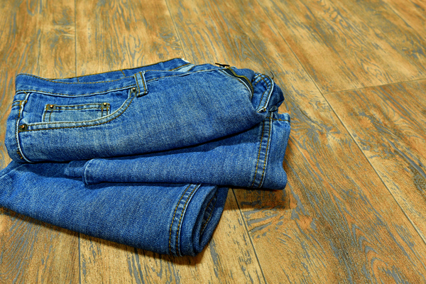 Mens jeans on the floor: Men's pair of jeans lying on the wooden floor .