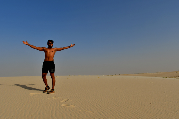 Young adult enjoying the sun: Young adult man, is sitting on the sand hill in desert area and he is enjoying the sand and sunlight. His slim body suggests that he is a fitness model working out daily to maintain a healthy life style and healthy living habits.