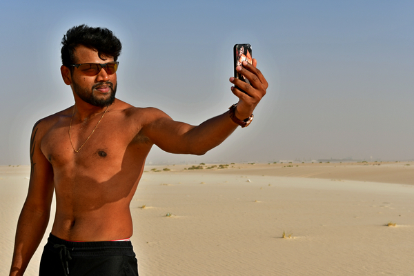 Man loves making a selfie: Young adult man, is taking a selfie photo on the sand hill in desert area and he is enjoying the sand and sunlight. His slim body suggests that he is a fitness model working out daily to maintain a healthy life style and healthy living habits. Selfie addi