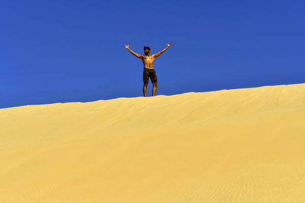 Jogging on a Desert Dune: Fitness model is running on desert dunes for practice, for good health and to maintain his perfect body. Sand and sky only in the photo and the young adult is having a great time and enjoying his life.