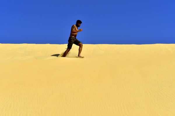 running on a Desert Dune: Fitness model is running on desert dunes for practice, for good health and to maintain his perfect body. Sand and sky only in the photo and the young adult is having a great time and enjoying his life.
