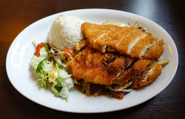 breaded chicken breast: breaded chicken breast with salad and rice, served on vegetables and glass noodles (aka sukiyaki)