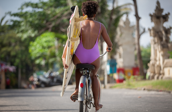 Surfer girl riding bicycle: Beautiful surfer girl in purple bikini with afro hairstyle riding bicycle with one hand, carrying surfboard under her arm at Kuta beach, Bali, Indonesia