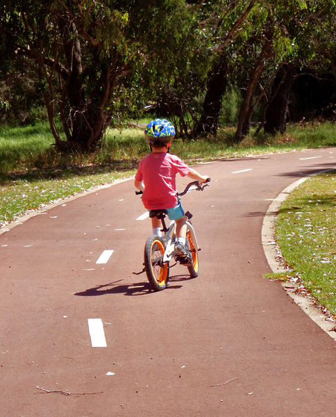 on the cycle path1: young boy bicycling on public park cycling path
