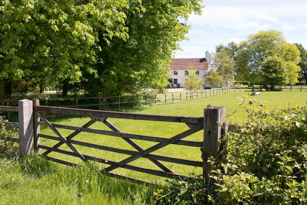 Rural gate and house: View in spring of a rural gate and house in Surrey, England.