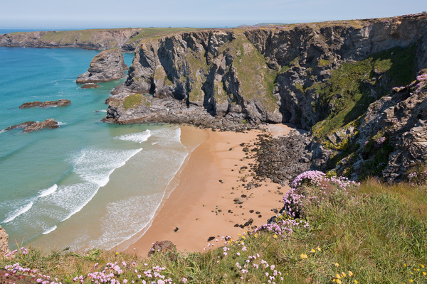 Beach from above: A sandy beach between cliffs on the coast of Cornwall, England.