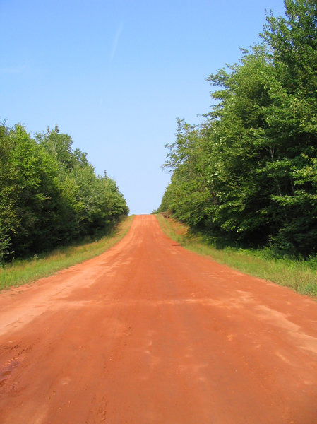 Long Road Ahead...: Red dirt road in PEI, Canada -- such a beautiful province!  Apparently the dirt's rich red hue is due to its naturally occurring high iron oxide content.  :-)Please let me know if you are able to use my pictures for something.Even if it's something small