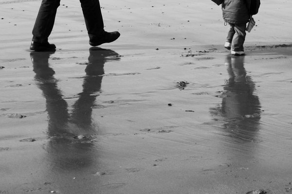 reflections at the beach: a man and a child walking at the beach, reflected in the wet sand.