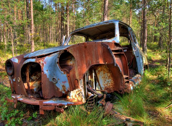 Disintegration - HDR: Old car in a forest in Sweden. The car is, I believe, an old Saab. The picture is HDR using five images.