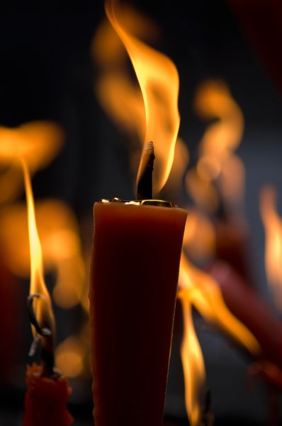 Candles: close-up of a burning candle in a temple