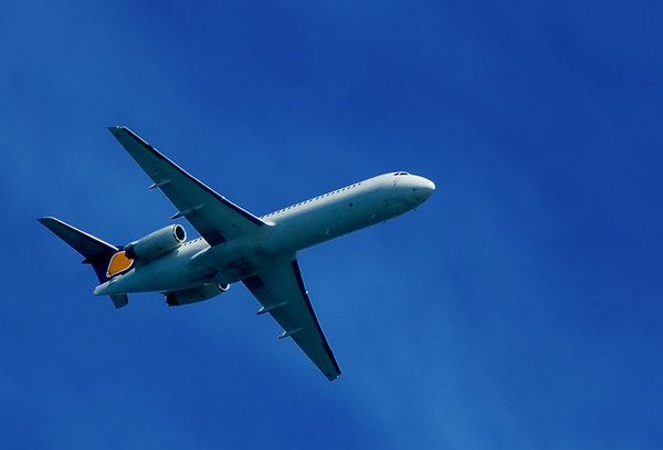 Airplane Flying: Airplane flying over a blue sky seen from below - side