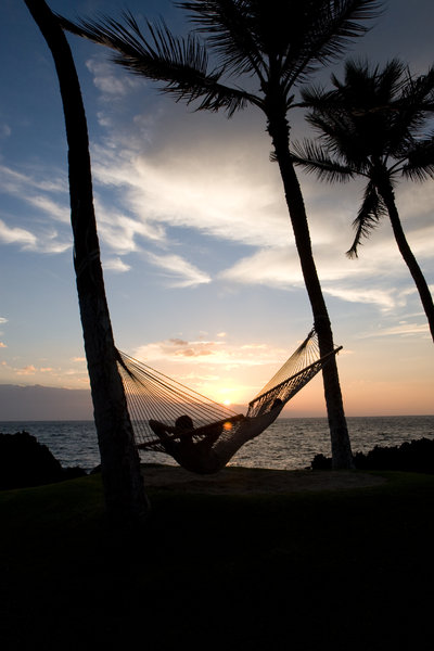 A time to take it all in: Adult relaxes on Hammock during sunset in Hawaii