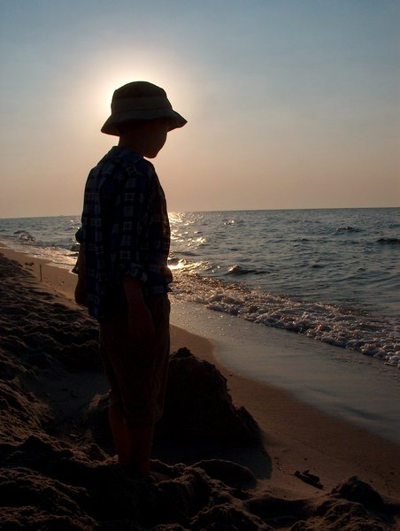 Child and sunrise by the sea: Kid watching at sunrise