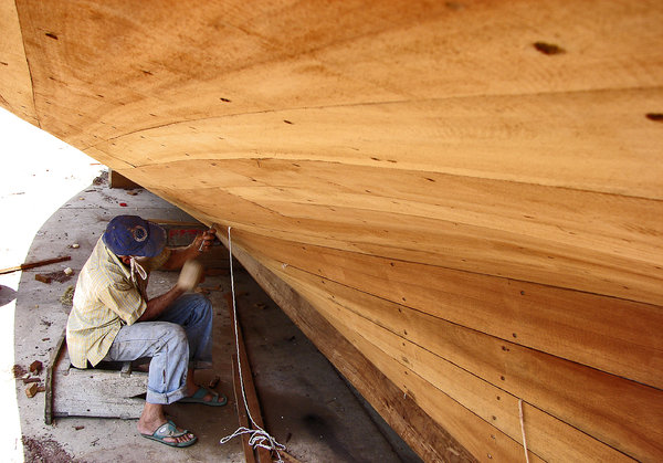 Caulking: An old artisan shipwright at work on a Bongo (medium sized fishing boat used locally. Typical Measurents: LOA: 14 Mts. Beam: 4.4 Mts. Inboard diesel engine)  in Punta de Palmas, Oriental coast of the Maracaibo lake, Venezuela.