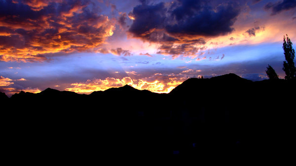 Crimson Skies: The setting sun paints the sky. Leh Town.