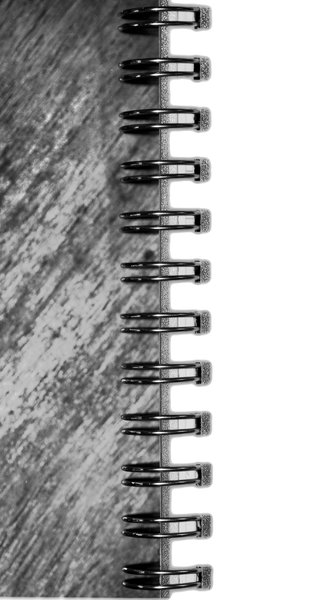 Spirals and Wood: Macro shot of the edge of a spiral bound pad on a wooden table, converted to black and white.