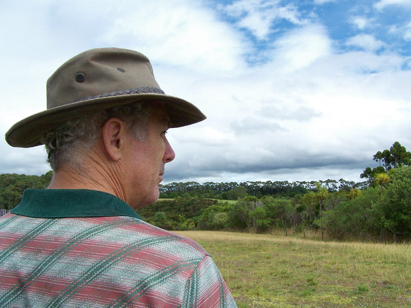 Just a farmer looking out over: Man looking out over the farmland, watching the weather