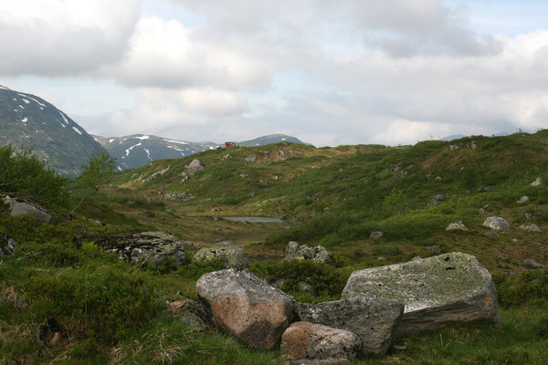 Little red house: Wild terrain in Norway, with an isolated house in the distance.