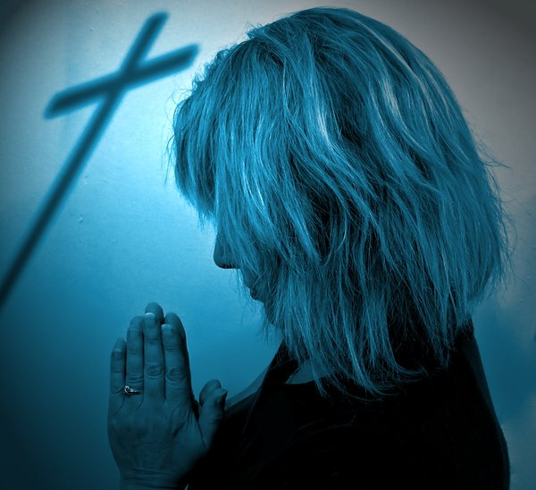 Easter Prayer 2 Duotone: A woman praying, with the shadow of a cross in the background. Blue tones, special light.