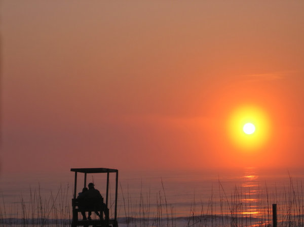 Lovers Dawn: Sorry, another sunrise, but I couldn't resist! A close couple enjoying the break of a new day on a lifeguard seat at the beach. Original - renamed