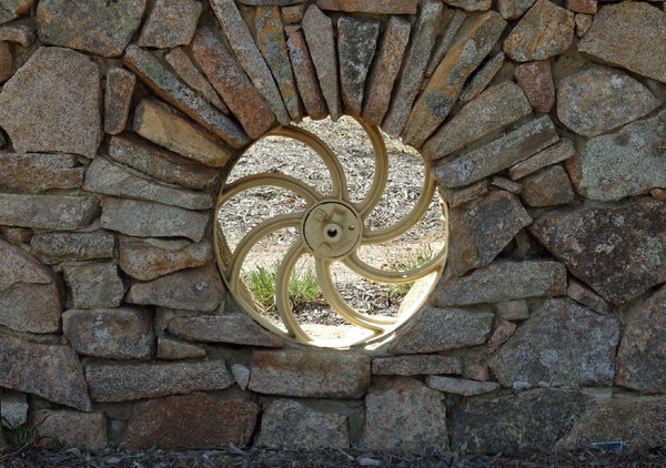 wheeled hole in the wall: circular farm machine wheel embedded in stone wall