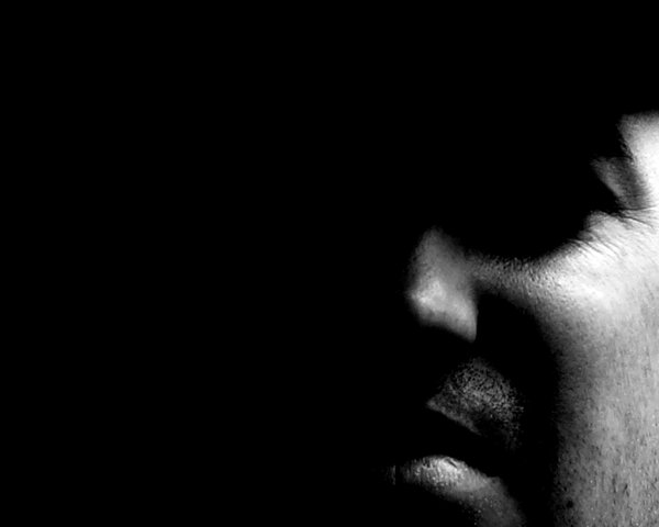 Man's Face in Shadows 1: A male face, heavily shadowed. Can be used to illustrate interest or darker emotions. Plenty of copyspace.