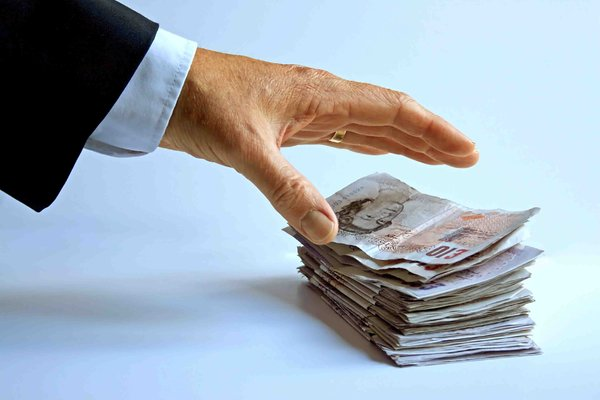 Cash Grab: A hand grabs at a pile of sterling bank notes