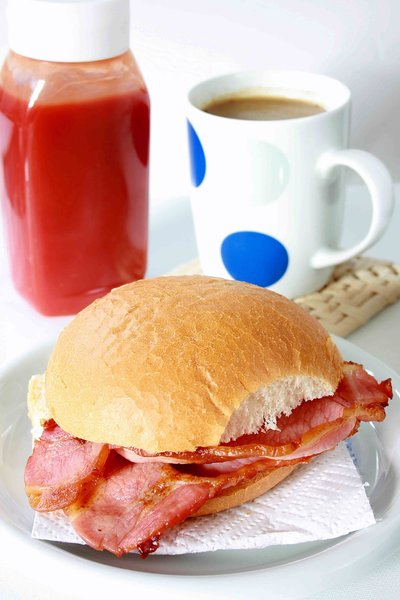 Bacon Roll: Fried bacon roll with a mug of tea and tomato sauce