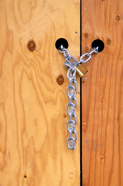 Lock and Chain: Lock and chain on a door at a construction site.