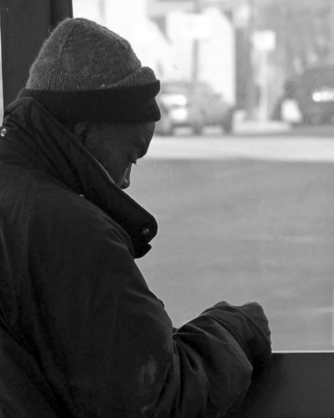 Bus Shelter: Homeless man using bus shelter as shield against cold wind