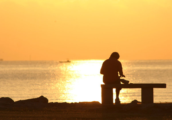 Bible Reader: Man reading his bible at sunrise on Galveston Bay