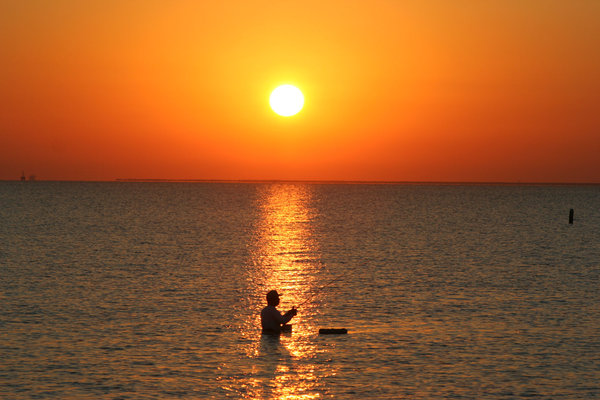 Sunrise with a Fisherman: Man fishing at sunrise