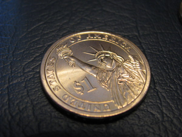 "In God We Trust: The new dollar coin they came out with, this one sitting pointedly on my check book.Instead of putting ""In God We Trust"" on the face of the coin they put it on the outside edge- where it'll wear off. I thought that was interesting."