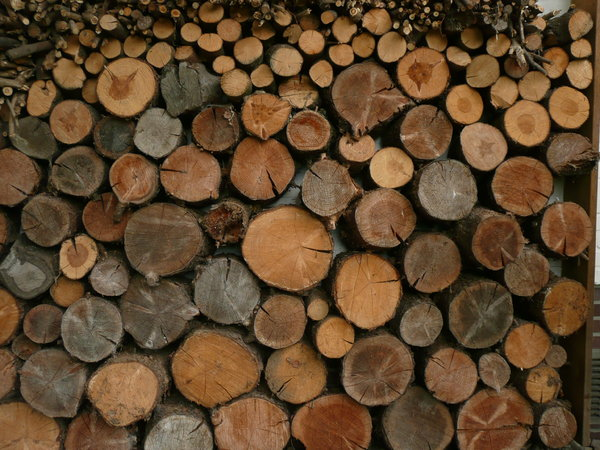 Stack of Wood: Stack of Wood on a house wall for heating the fireplace
