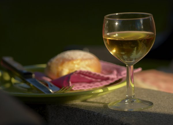 Glass of wine.jpg: a glass of white wine, baked cake in background