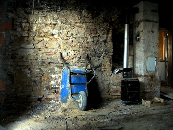 blue barrow: A blue barrow in front of a stone wall in the House Conrath in Karlsbad/Germany during the restoration