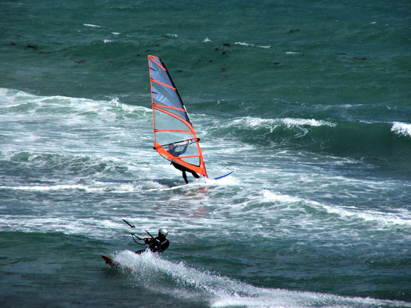 sailing through the surf: surf glider - kite surfer and wind surfer passing each other in the water