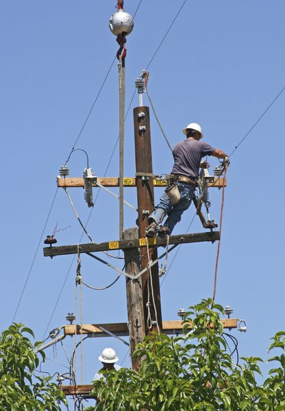 Men Replacing Power Pole: A crane drops a new power pole into a hole next to the one they are replacing. These workers transfer the hardware and hook up the wires to the new pole.
