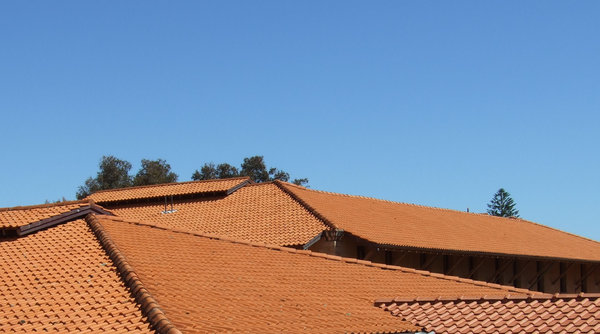 Orange & blue - roof tile angl: orange roof tiles and roofing angles against blue sky
