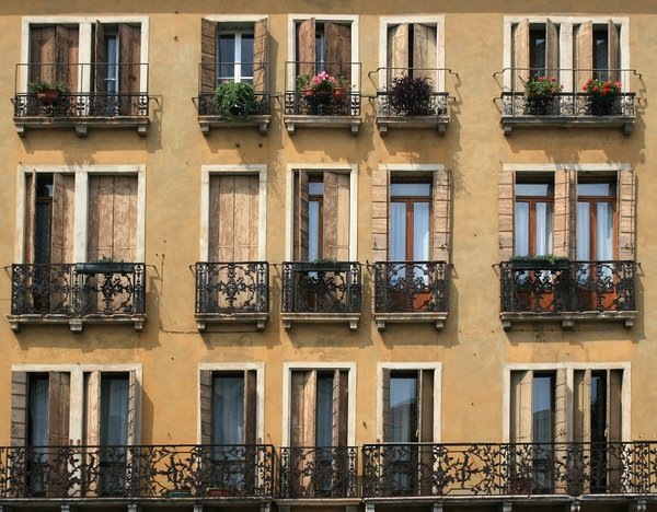 Windows and balconies: Windows and balconies of a large tenement in Italy.