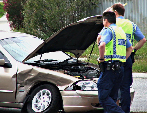 checking the damage: police checking the damage to a motor vehicle involved in a crash
