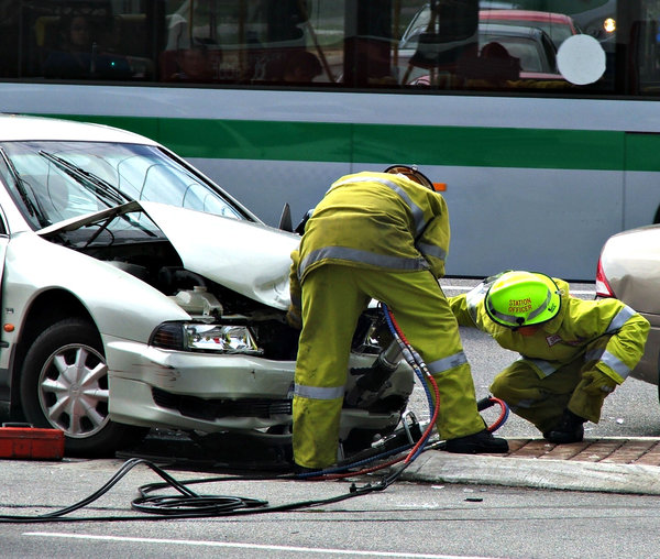 fire & rescue at work: firemen using jaws of life to open tangled car metal at accident scene with bus passing by