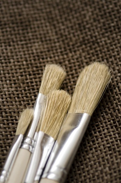 Brushes on canvas: Paint brushes on dark canvas
