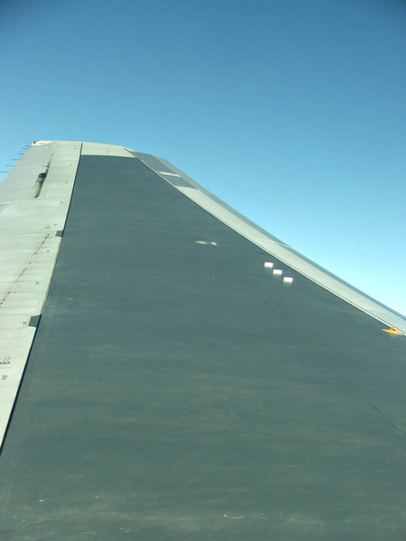 wingtip to space: looking along airplane wing while flying at high altitude