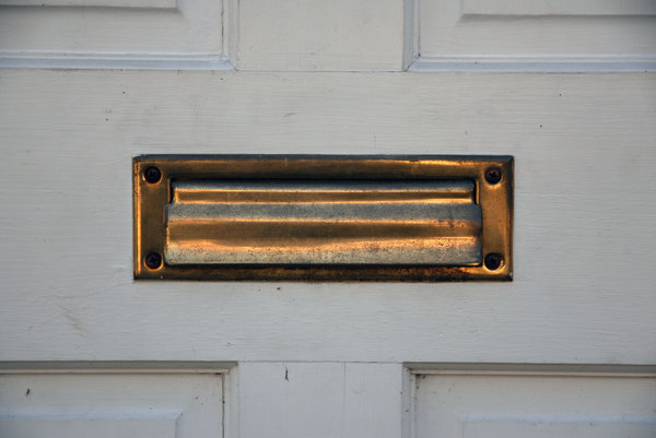 Mail Slot: A mail slot in a door.