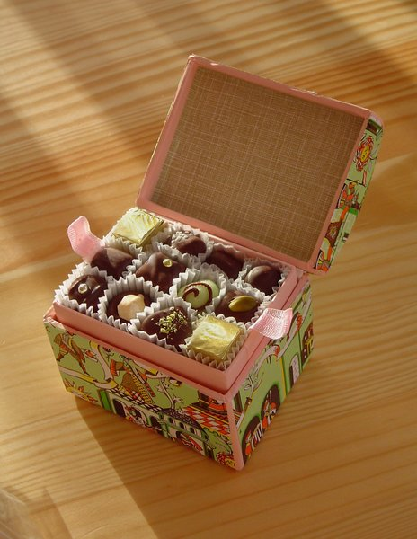 Sweet box: Box of filled mini chocolates on wooden table