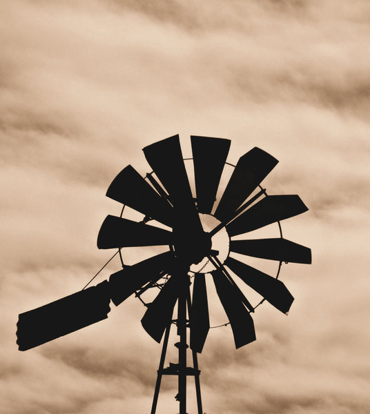 old windmill silhouette: sepia image of old farm windmill silhouette